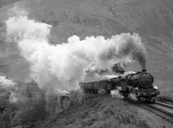 Photograph by Cyril Herbert showing a steam locomotive pulling an express train in the West Highlands of Scotland