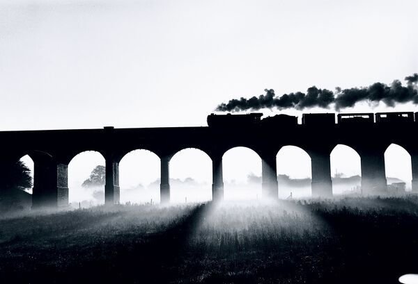 Photograph by John Click. This atmospheric picture shows a Class K3 2-6-0 locomotive heading north across a viaduct, pulling a train of cattle trucks, silhouetted against the sun which shines through the early morning mist beneath the viaduct's