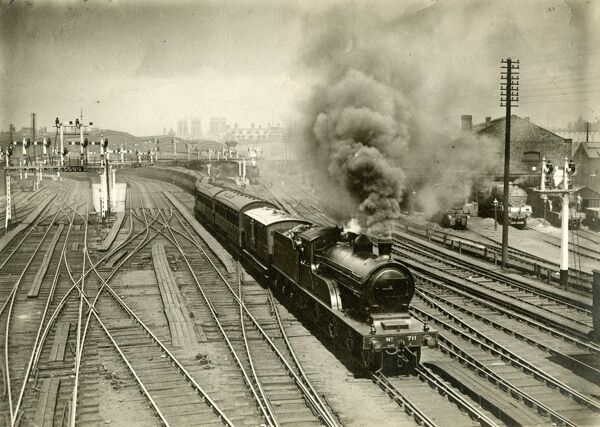 York station, London & North Eastern Railway. View from the south of a train leaving the station. The locomotive is ex-North Eastern Railway class R 4-4-0 no. 711, built Gateshead 1906, renumbered 2374 in 1946, scrapped 1948. About 1910