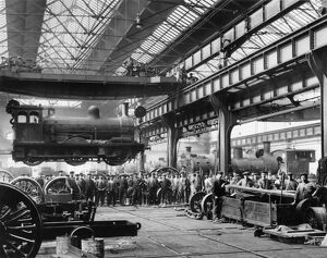 Crowds watching a suspended locomotive at the North Eastern Railway's Gateshead Works