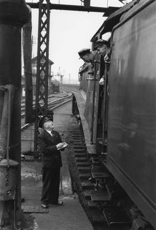 Driver and fireman consulting with station guard, c 1956
